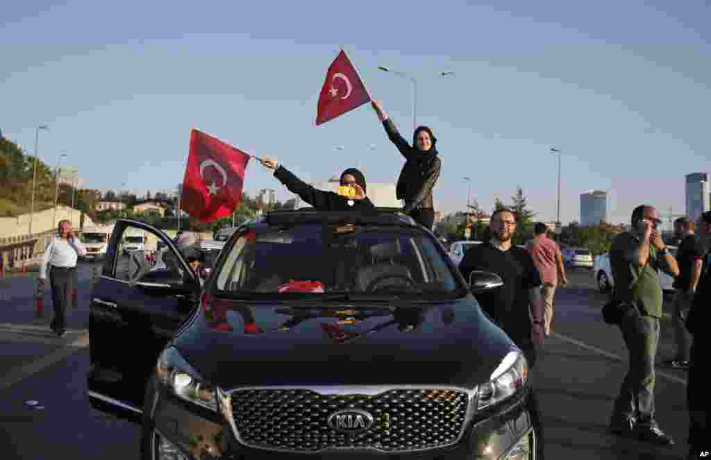 Turkish people wave the national flags on a car in Istanbul, Turkey, Saturday, July 16, 2016.
