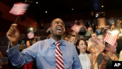 Seorang warga keturunan Haiti melambaikan bendera AS dalam upacara naturalisasi di Miami. (Foto: Dok)