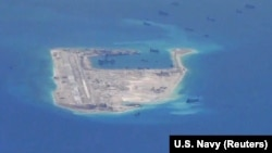 FILE - Chinese dredging vessels are purportedly seen around Fiery Cross Reef in the disputed Spratly Islands in the South China Sea in this image from video taken by a P-8A Poseidon surveillance aircraft provided by the U.S. Navy, May 21, 2015.