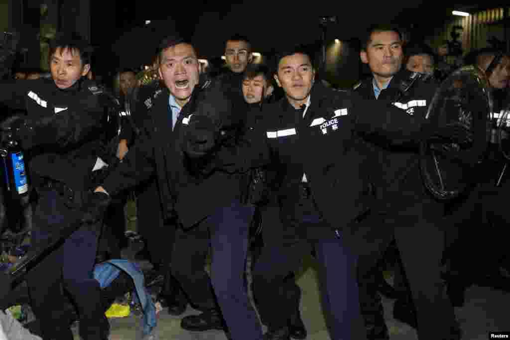 Polisi berteriak pada para demonstran ketika bereka berusaha masuk ke Badan Legislatif di Hong Kong, 19 November 2014.