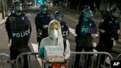 Sinh viên trường luật Alyson Reimer cầm tấm bảng phản đối trong cuộc biểu tình trong khi cảnh sát phong tỏa con đường trước trụ sở cảnh sát ở Berkeley, California, 8/12/14