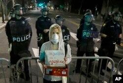 دانشجوی رشته حقوق دانشگاه برکلی، آليسون ريمر، با در دست داشتن پلاکاردی به کشتار دوسياهپوست در ميسوری و نيويورک توسط پليس اعتراض میکند. پشت سر او ماموران خيابان روبروی پاسگاه پليس برکلی در کاليفرنيا را بستهاند.