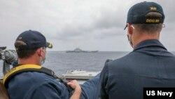 """美國海軍公佈的照片顯示,兩位美國海軍中校羅伯特·J·布里格斯與理查德·D·斯萊2021年4月4日在阿利·伯克級導彈驅逐艦""""馬斯廷號""""駕駛艙進行水面接觸觀察。照片中可見中國""""遼寧號""""航空母艦及其舷號。"""