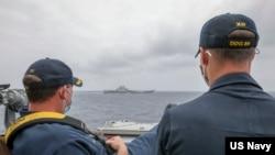 """资料照片:美国海军公布的照片显示,两位美国海军中校罗伯特·J·布里格斯与理查德·D·斯莱2021年4月4日在阿利·伯克级导弹驱逐舰""""马斯廷号""""驾驶舱进行水面接触观察。照片中可见中国""""辽宁号""""航空母舰及其舷号。"""