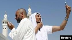 Seorang jemaah haji berdoa sementara yang lainnya melakukan swafoto atau selfie di Masjid Agung saat melakukan tawaf di Makkah. (Foto: Dok)