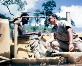 A Peace Corps Volunteer works with a Tanganyikan caterpillar driver on the Great Ruaha road project. They are working to better access a sugar refinery.(1962)