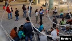 Para migran asal Amerika Tengah menunggu proses imigrasi terhadap permohonan suaka mereka di El Paso, Texas, AS (29/3).