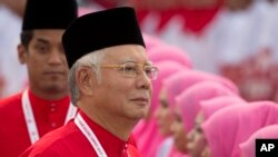 FILE - President of the ruling United Malays National Organisation (UMNO) and Malaysia's Prime Minister Najib Razak inspects a ceremonial guard of honor.