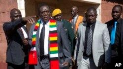 Presiden Zimbabwe Emmerson Mnangagwa (kedua dari kiri) meninggalkan TPS setelah memberikan suara dalam Pilpres di kota Kwekwe, Senin (30/7).