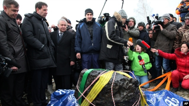 People look at what scientists believe to be is a chunk of the Chelyabinsk meteor, recovered from Chebarkul Lake near Chelyabinsk, about 1500 kilometers  east of Moscow on October 16, 2013.