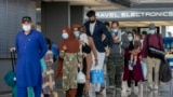 FILE - Families evacuated from Kabul, Afghanistan, walk through the terminal to board a bus after they arrived at Washington Dulles International Airport, Aug. 31, 2021, in Chantilly, Va.