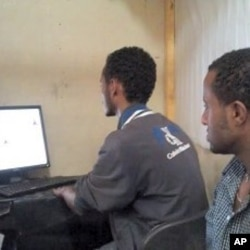 Computer technician Zelalem Tadesse fills out the DV2013 diversity visa form for Yusuf Tamiru at an Addis Ababa internet cafe, Ethiopia, October 31, 2011.