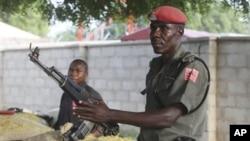 ພວກເຈົ້າໜ້ທີ່ຕໍາຫລວດທີ່ຖືອາວຸດປືນ AK-47 ຢືນຍາມໃນຂຸມ ລີ້ໄພຂີ້ຊາຍແຄມຖະໜົນໃຫຍ່ສາຍນຶ່ງໃນເມືອງ at Maiduguri, ໄນຈີເຣຍ. ວັນທີ 5 ພະຈິກ 2011.