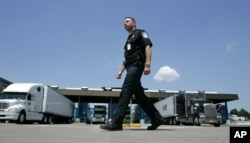 FILE - U.S. Customs and Border Protection officer Kevin Corsaro walks past a truck inspection station at the U.S. border in Buffalo, N.Y.