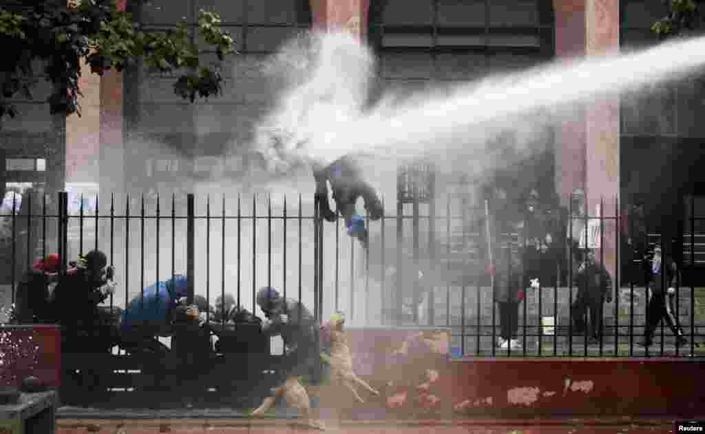 A student is hit by a jet of water sprayed by riot police during a protest against the government to demand changes in the public state education system, in Santiago, Chile.