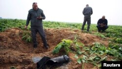 Israeli security forces stand next to the remains of a rocket that was fired from the Gaza Strip toward Israel on Friday, on the Israeli side of the border, Dec. 19, 2014.