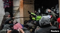 """FILE - Protesters clash with police at the west entrance of the Capitol during a """"Stop the Steal"""" protest at the U.S. Capitol in Washington, Jan. 6, 2021."""