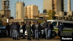 FILE - Police officers stand outside the Lonmin mine in Rustenburg, South Africa, May 14, 2014.