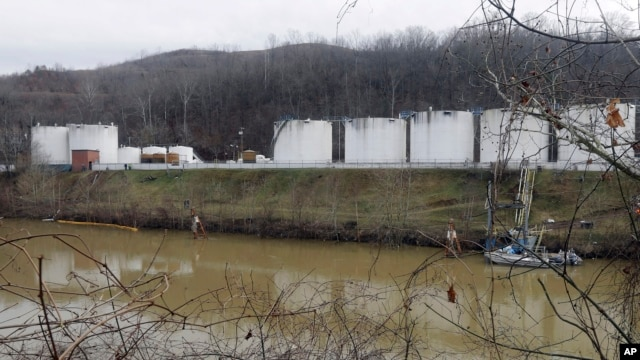 Workers inspect an area outside a retaining wall around storage tanks where a chemical leaked into the Elk River at Freedom Industries storage facility in Charleston, West Virginia, Jan. 13, 2014.