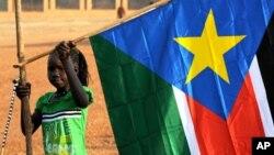 Msichana wa Sudan Kusini akishikilia bendera ya eneo hilo.