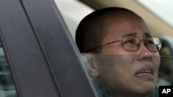 FILE - Liu Xia, wife of imprisoned Nobel Peace Prize winner Liu Xiaobo, cries in a car outside Huairou Detention Center where her brother Liu Hui has been jailed in Huairou district, on the outskirts of Beijing, China.