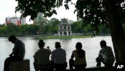 Người dân ngồi dưới bóng cây bên bờ hồ Hoàn Kiếm.