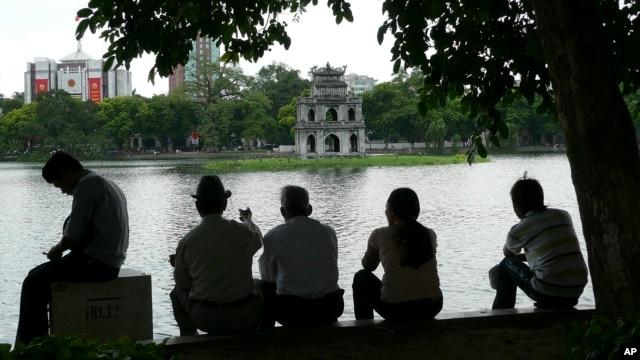Người dân ngồi dưới bóng râm để tránh nắng tại Hồ Hoàn Kiếm, Hà Nội, Việt Nam.