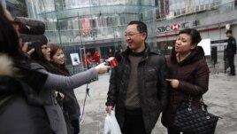 Los medios de comunicación entrevistan a un feliz comprador de un iPhone 5 en China.