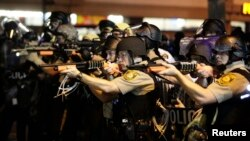 Police officers point their weapons at demonstrators protesting against the shooting death of Michael Brown in Ferguson, Missouri August 18, 2014. Police fired tear gas and stun grenades at protesters on Monday after days of unrest sparked by the fatal sh