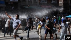 Nepalese protesters defying a government coronavirus lockdown to take part in a religious festival clash with riot police, in Lalitpur, Nepal, Sept. 3, 2020.
