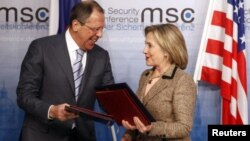 U.S. Secretary of State Hillary Clinton and Russian Foreign Minister Sergei Lavrov exchange documents formally bringing into force the landmark nuclear arms reduction pact START during the 47th Conference on Security Policy in Munich February 5, 2011. R