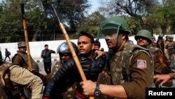 Polisi menahan seorang pria tak dikenal setelah dia mengacungkan senjata dan melukai seorang siswa saat berlangsungnya aksi protes terhadap UU kewarganegaraan baru di luar universitas Jamia Millia Islamia, New Delhi, India, 30 Januari 2020.