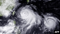 This NOAA photo shows two typhoons in the Philippine Sea and a tropical storm near the China coast near Hong Kong and Macau which have the region on alert, taken July 10, 2015.