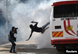 A supporter of Kenyan opposition leader Raila Odinga of the National Super Alliance (NASA) coalition jumps from a bus after riot police fired tear gas canisters to disperse them after his swearing-in ceremony in Nairobi, Jan. 30, 2018.