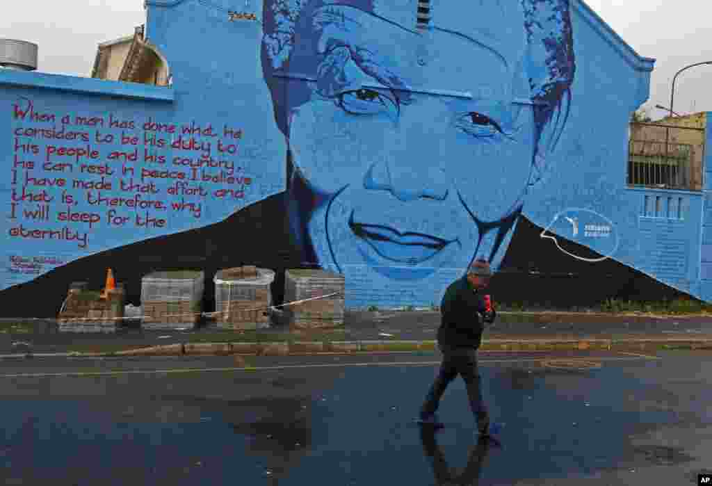 A woman walks past a mural with the face of former South African President Nelson Mandela in Cape Town, South Africa, July 18, 2014.