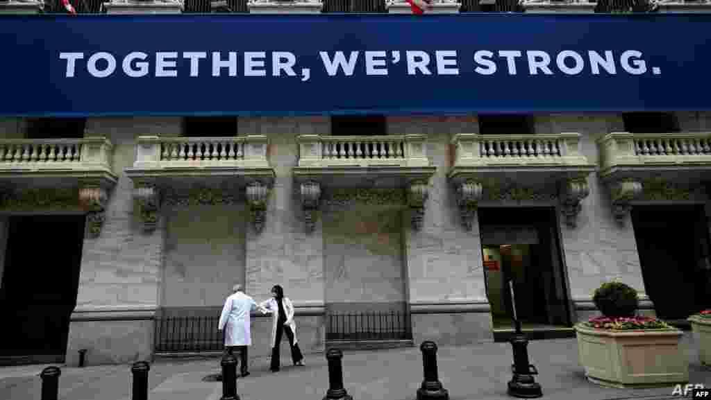 두 달 만에 개장한 미국 뉴욕증권거래소 앞에서 의료 관계자들이 팔로 인사를 나누고 있다.