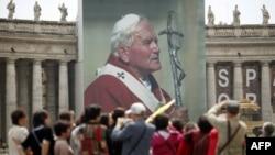 Tín đồ Công giáo bên cạnh tấm ảnh của Đức cố Giáo Hoàng John Paul II tại Quảng trường Thánh Phê-rô