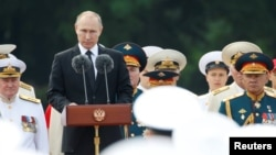 FILE - Russian President Vladimir Putin delivers a speech during the Navy Day parade in St. Petersburg, Russia, July 30, 2017.