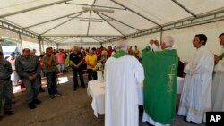 The bishop of Ascoli Piceno, Giovanni D'Ercole, celebrates mass in a tent camp set in Pescara del Tronto, near Amatrice, central Italy, Aug. 28, 2016.