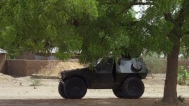 A military armored vehicle is stationed under a tree during a military patrol in Hausari village, near Maiduguri Jun. 5, 2013.