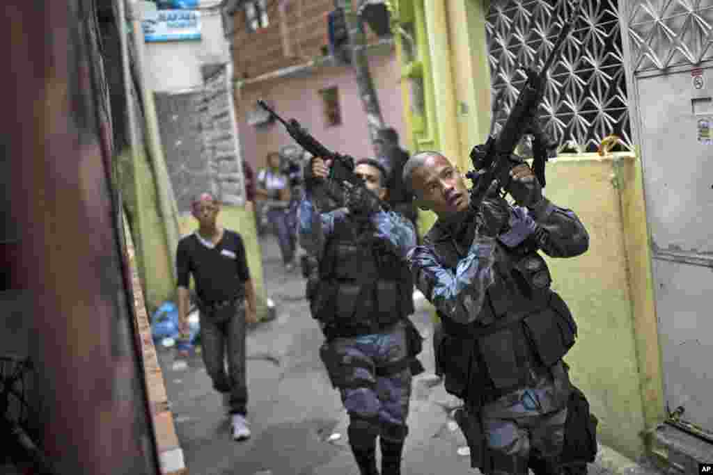 Military police officers patrol in the Roquette Pinto shantytown, part of the Mare slum complex in Rio de Janeiro, Brazil.