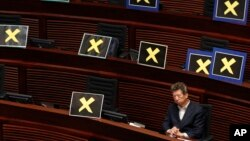 Pro-democracy lawmaker Ronny Tong sits among seats filled with yellow crosses placed after lawmakers walked out of the legislative chamber to protest against Chief Secretary Carrie Lam who presented details of a Beijing-backed election plan, in Hong Kong.