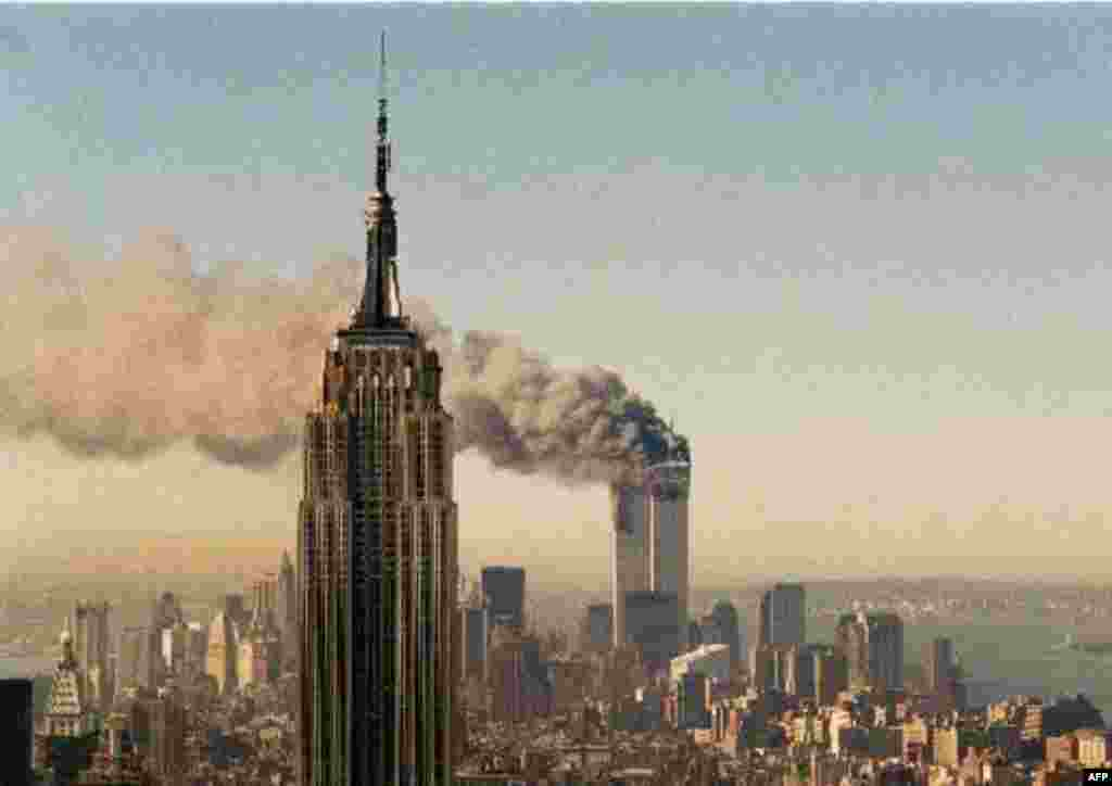 The twin towers of the World Trade Center burn behind the Empire State Building in New York, Tuesday, Sept. 11, 2001. In a horrific sequence of destruction, terrorists crashed two planes into the World Trade Center and the twin 110-story towers collapsed.