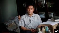 资料照:中国维权律师浦志强在便衣警察关注下在北京的办公室对媒体讲话。(2009年6月1日)