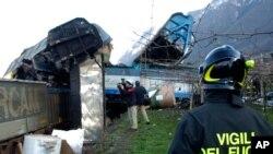 Un pompier regarde deux trains de marchandises entrés en collision dont les conducteur ont été tués près de la gare Borghetto sull'Adige dans le nord de l'Italie, 13 décembre 2006. (AP Photo / Daniele Mosna)