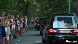 People pay their respects as a convoy of hearses, bearing remains of the victims of the Malaysia Airlines Flight MH17 crash, drive past in Hilversum, Netherlands, July 23, 2014.