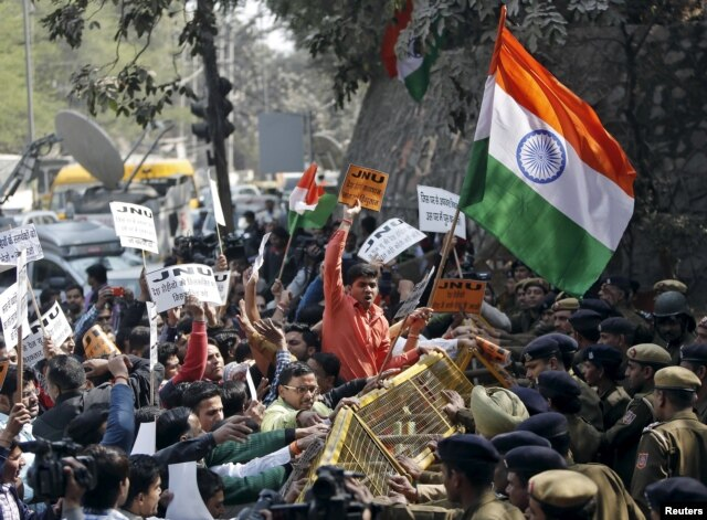 Activists from various Hindu right-wing groups shout slogans as they try to cross a police barricade during a protest against the students of Jawaharlal Nehru University outside the university campus in New Delhi, India, Feb. 16, 2016.