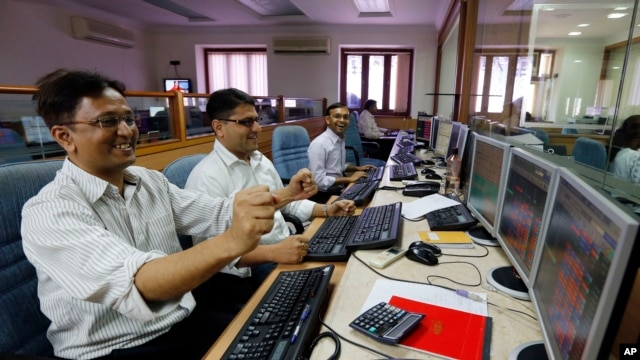 FILE - Indian stockbrokers celebrate as they watch the Bombay Stock Exchange (BSE) index on their trading terminal in Mumbai, India.