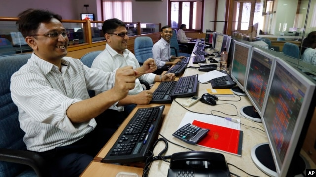 Indian stockbrokers celebrate as they watch the Bombay Stock Exchange (BSE) index on their trading terminal in Mumbai, India, May 13, 2014.