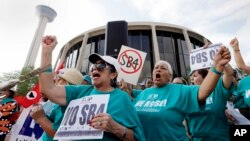 FILE - Lydia Balderas, left, and Merced Leyua, right, join others as they protest against a new sanctuary cities bill outside the federal courthouse in San Antonio, June 26, 2017.